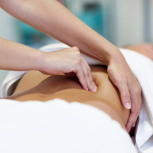 Female patient is receiving treatment by professional osteopathy therapist. Woman having abdomen massage in a physiotherapy center.